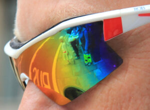 a closeup of a person wearing rainbow sunglasses. The reflection of a group of people waiting to cross the street can be seen in them.