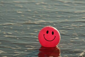a red beach ball floating in the ocean