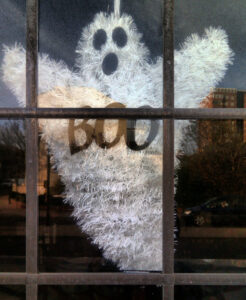 """a ghost decoration inside a window. It has """"boo"""" written on its chest"""