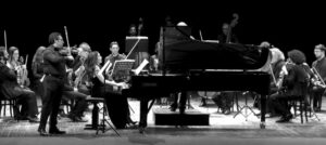 a black and white photo of an orchestra in concert