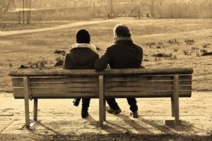 a sepia toned photograph of two people sitting on a park bench, viewed from behind