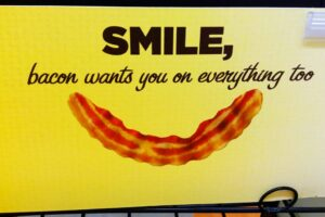 """it's a poster that says """"smile, bacon wants you on everything too"""" and has a bacon strip that's curved into the shape of a smile"""