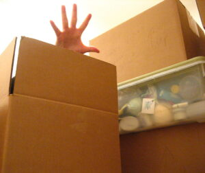 a hand reaching out of a packed moving box