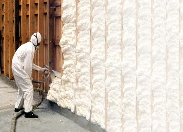 someone in a white suit spray foaming into insulation