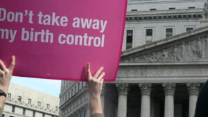 """a pink sign being held up that says """"Don't take away my birth control"""" in front of a building"""