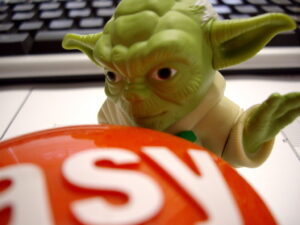 a yoda doll standing on a desk with a keyboard in the background. The Yoda doll is standing in front of a big red button that says easy, with his hand raised as though he is about to hit it