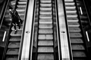 a black and white photo of a row of escalator with only a single person riding any of them