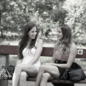 a couple of long haired people talking while sitting on a park bench