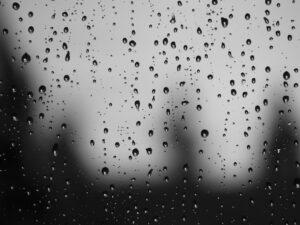 a black and white photo of rain on a windowpane