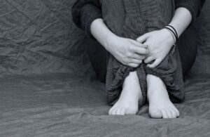 a person sitting with their hands wrapped around their knees (you can't see their face)