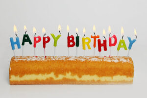 """a Twinkie with lit alphabet candles sticking out of it that spell out """"happy birthday"""""""