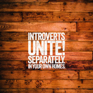 """a wooden background with the words """"Introverts Unite! Separately in your own homes"""" over it"""