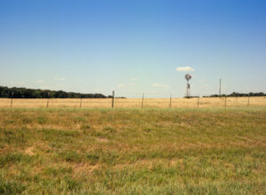 a ranch in North Texas. Wide blue open sky with few clouds. A windmill. Prairie grass. A fence.