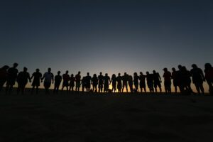 the silhouettes of a few dozen people standing on a beach holding hands