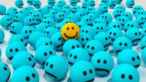 one yellow smiley face ball in a sea of blue sad face balls
