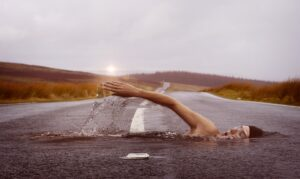 a surreal image of a woman swimming through a road