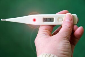 a hand holding an electronic thermometer which reads 38.75 degrees