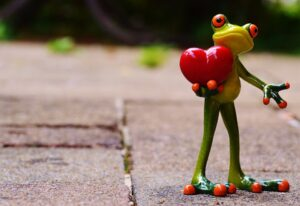 a figurine of a frog holding a heart