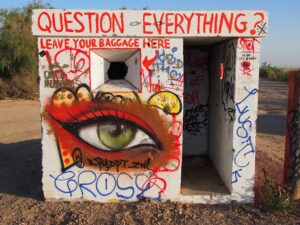 """a small concrete building with graffiti on it. Graffiti says """"Question Everything?"""" and """"leave your baggage here. Also has some illegible words as well as a large spraypainted depiction of an eye"""