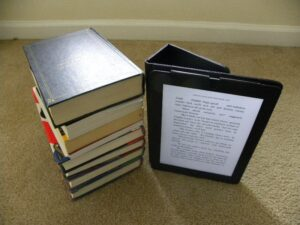 a stack of books and an e-reading device