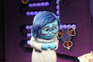a mascot from a theme park dressed in a costume of Sadness from the Pixar film Inside Out