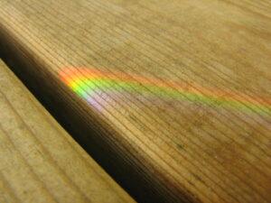 a bit of rainbow shining on wooden floorboards