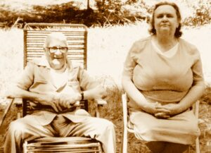 a sepia tinged photo of an elderly couple sitting outside on lawn chairs