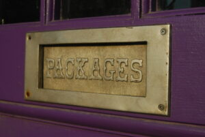 """a brass sign on a door that says """"packages"""""""
