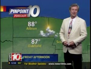 a TV weatherman standing in front of a forecast map