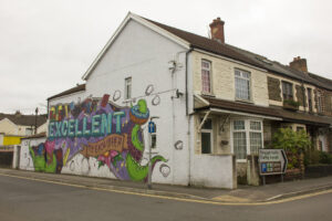 """a house with a colorful abstract mural painted on its side that reads """"Be Excellent to Each Other"""""""