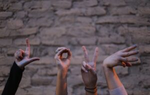 """4 hands spelling out """"L-O-V-E."""" The hands appear to all belong to different people"""
