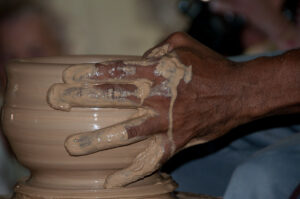 a potter's hands working a pot on the wheel