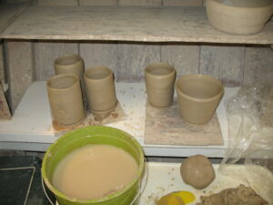 greenware cylinders on a drying shelf with a bucket of water nearby and some clay
