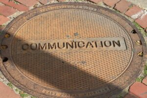 "a manhole that says ""communication"" on it"