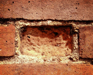 a brick wall with a brick missing