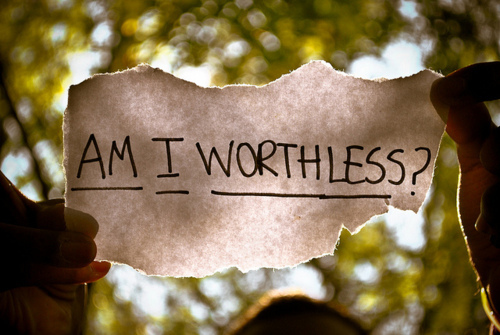 """Photo of two hands holding up a slip of paper with the words """"Am I worthless?"""" written on it"""