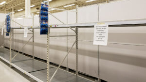 """empty store shelves. There are signs taped to them that read """"Due to increased demand, we are temporarily out of bathroom tissue. We apologize for the inconvenience."""