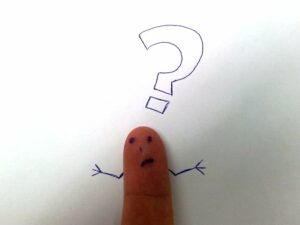 a finger with a confused face drawn on it on a background of a white sheet of paper. The finger figure also has stick arms drawn on the paper next to it that are in a confused/shrugging position. Over this stick figure's head is a question mark, also drawn on the white paper.