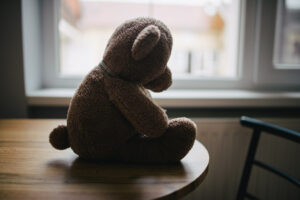 a teddy bear sitting on a table in profile in shadow