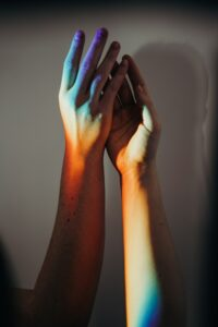 photo of 2 hands doing a high five motion, filtered behind rainbow light