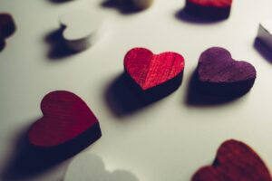 a handful of red wooden hearts scattered across a white surface
