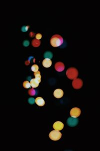 an abstract array of multiple multi-colored dots scattered in a haphazard fashion across a black background