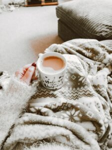 a photo that shows a person's hand holding a cup of coffee while their legs appear to be covered in a blanket as they sit on a couch