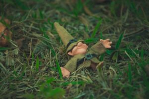 a gnome doll wearing a green pointy hat with buckled and green buckled coat and brown pants lying supine in grass