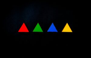 a red triangle, a green triangle, a blue triangle, and a yellow triangle all in one straight line, over a black background