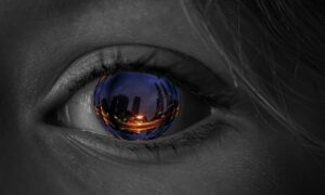 closeup of an eye with a city reflected back in the iris