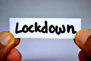 """hands holding a small sign that says """"lockdown"""""""