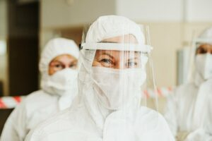 people in full-body personal protective equipment