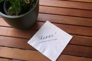 """an envelope that has """"thanks!"""" written on it, on top of a table"""