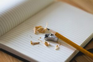 a sharpened pencil, pencil sharpener, and pencil shavings all sitting atop an open blank compositional notebook